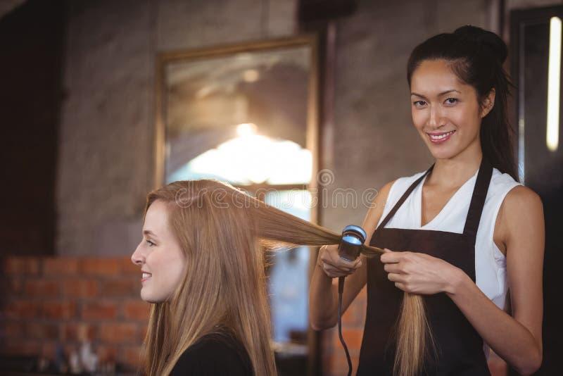 Vrouwelijke kapper die het haar van een cliënt rechtmaken stock afbeeldingen