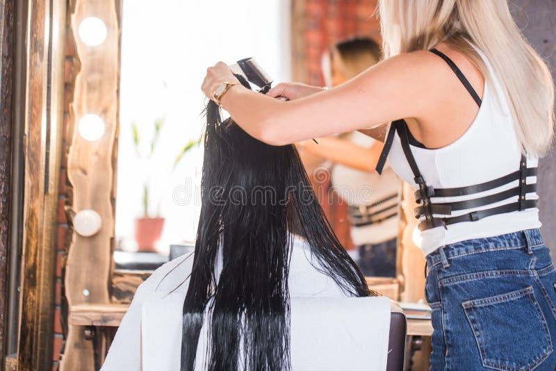 Vrouwelijke kapper die makend tot kapsel aan donkerbruine vrouw in salon glimlachen stock foto's