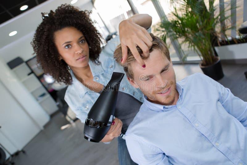 Vrouwelijke kapper die mannelijk klantenhaar drogen royalty-vrije stock fotografie