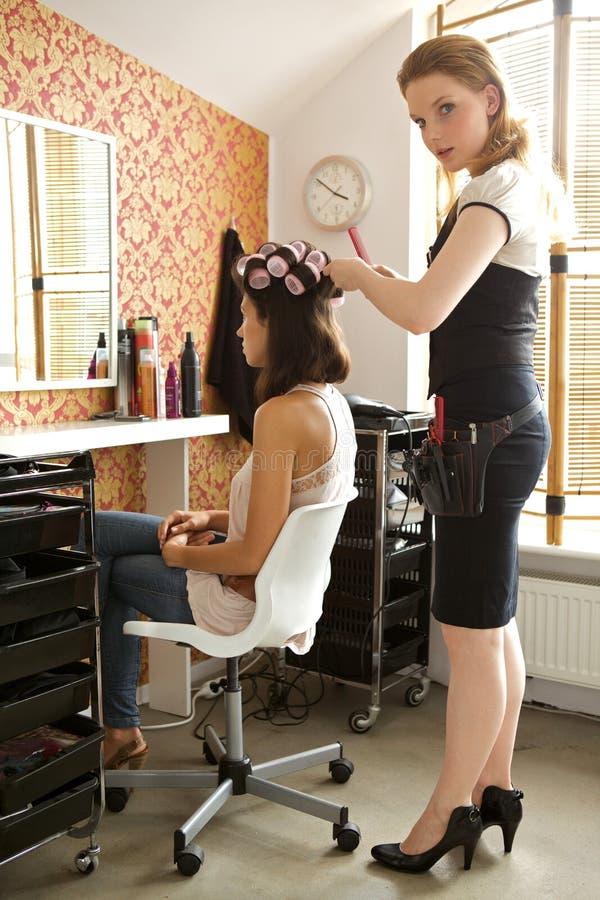 Vrouwelijke kapper het aanpassen krulspelden in het haar van de jonge vrouw royalty-vrije stock afbeeldingen
