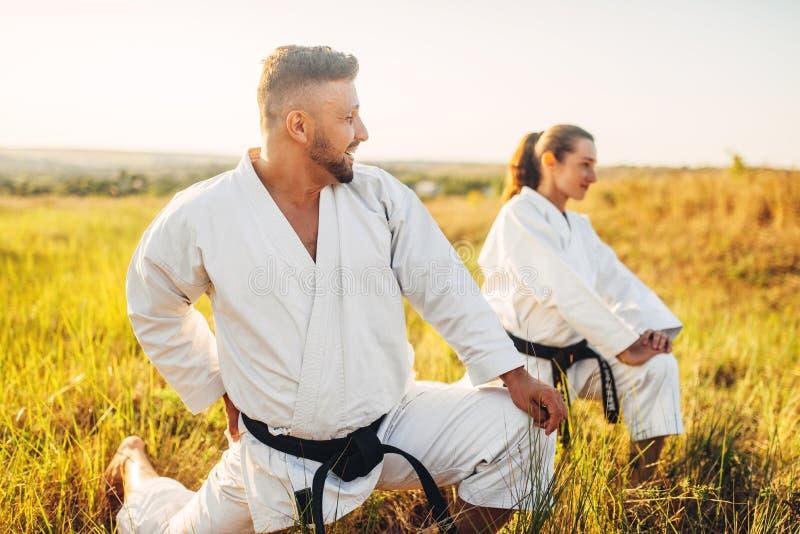 Vrouwelijke karate twee met mannelijke instructeur bij de opleiding stock fotografie