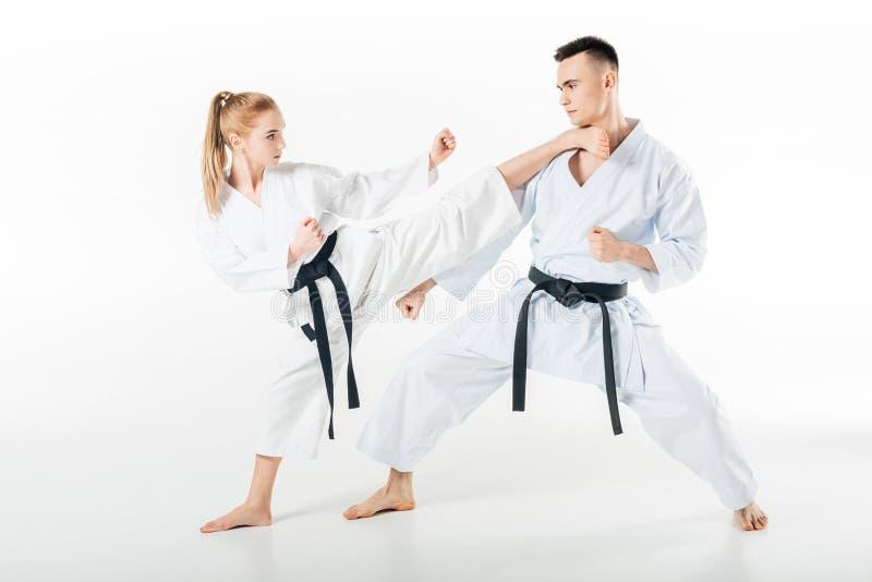 vrouwelijke karatevechter die mannelijke partner schoppen royalty-vrije stock fotografie