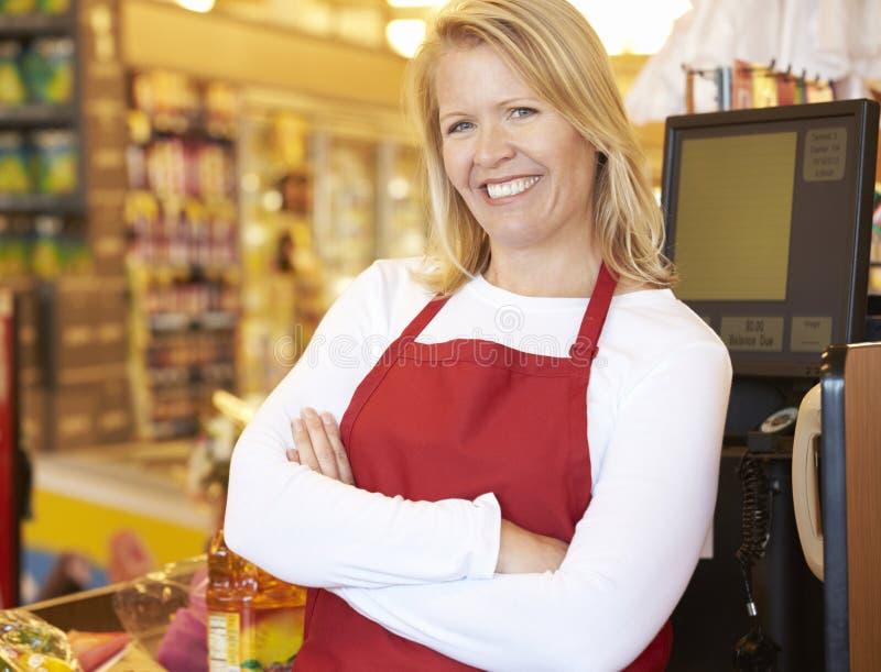 Vrouwelijke Kassier At Supermarket Checkout stock foto's