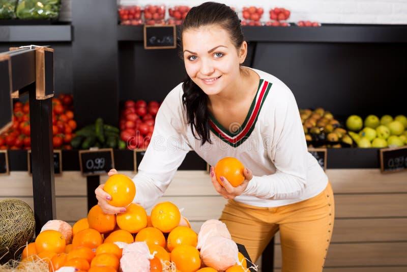 Vrouwelijke klant die diverse vruchten onderzoeken stock afbeelding