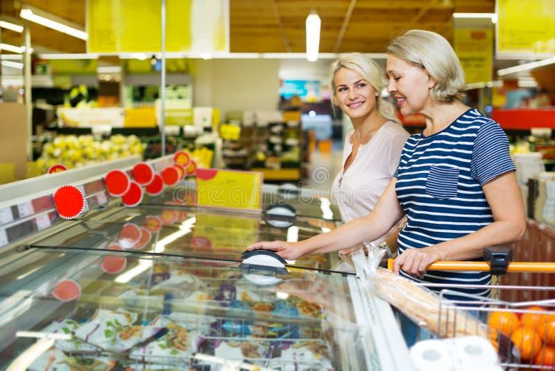 Vrouwelijke klanten dichtbij vertoning met bevroren voedsel stock afbeeldingen