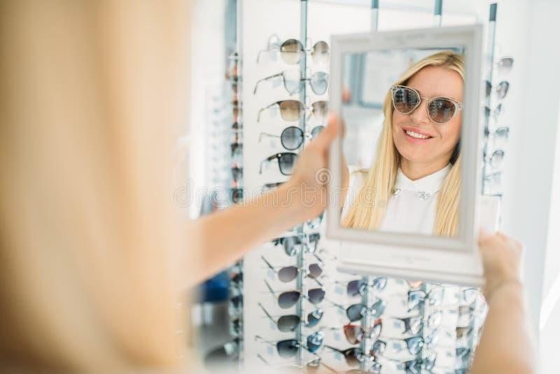 Vrouwelijke klanten shooses zonnebril in opticaopslag royalty-vrije stock fotografie