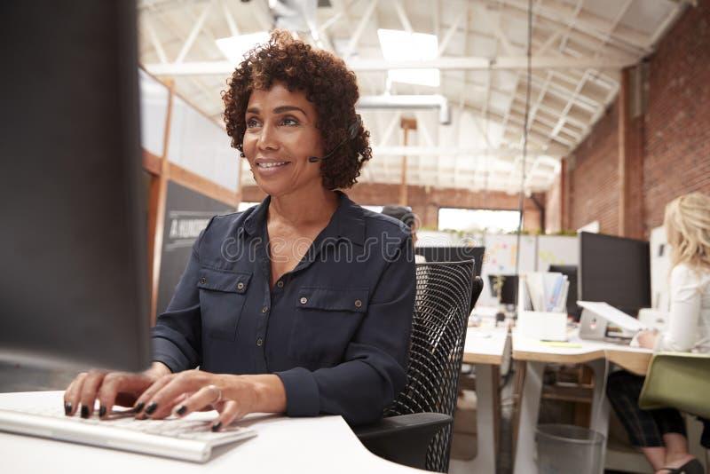 Vrouwelijke Klantenservicesagent Working At Desk in Call centre stock afbeelding