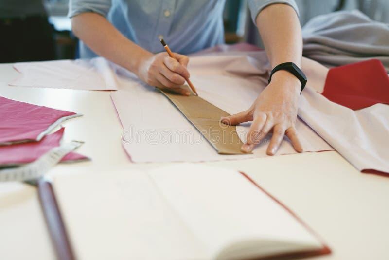 Vrouwelijke Kleermaker Making Sewing Patterns op Lijst stock afbeeldingen