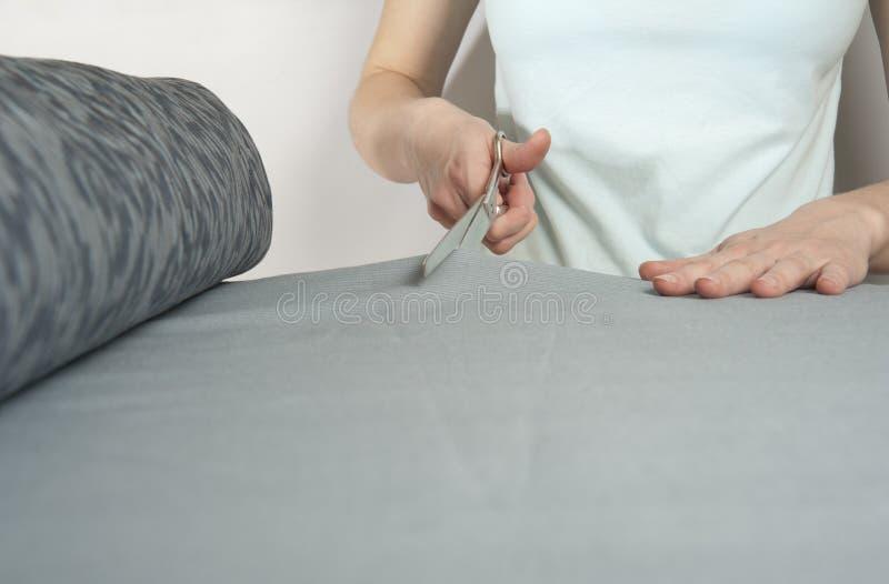 Vrouwelijke kleermakersbesnoeiingen met schaarbout van donkerblauwe doek Closeu royalty-vrije stock foto's