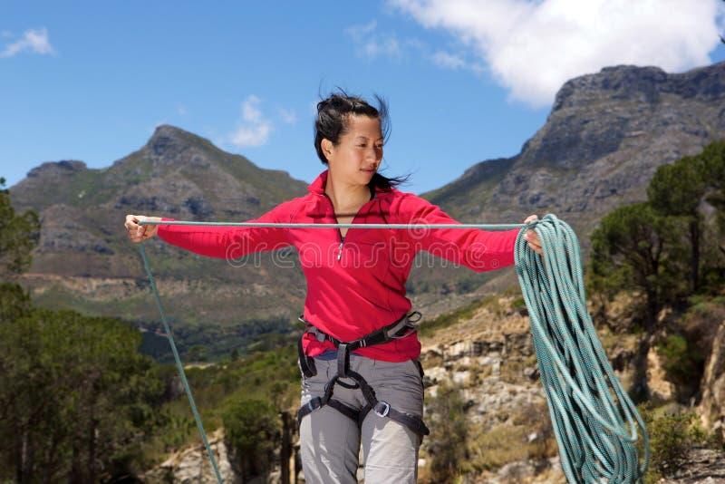 Vrouwelijke klimmer op de piek vouwende kabel stock foto's