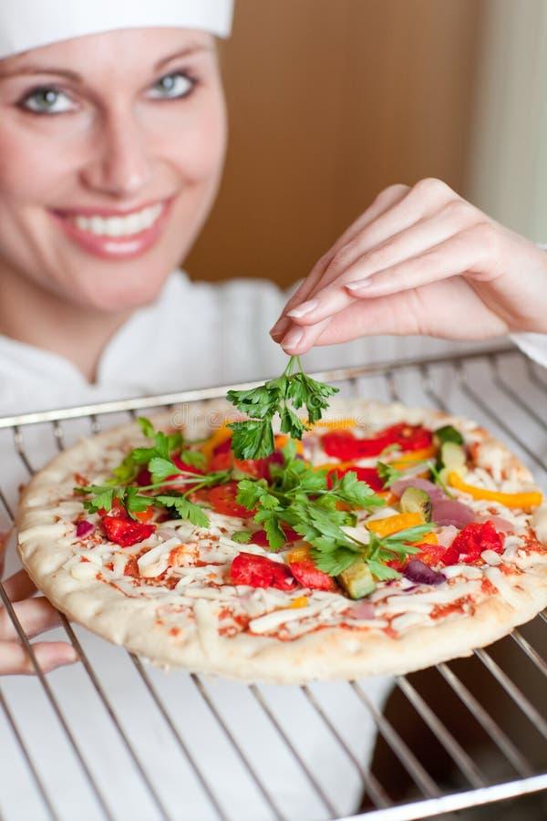 Vrouwelijke kok die peterselie op een pizza toevoegt royalty-vrije stock foto