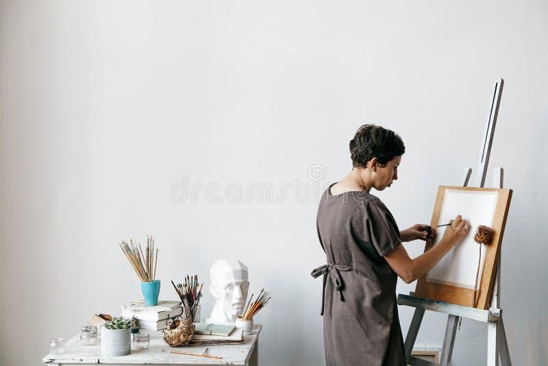 Vrouwelijke kunstenaar in haar ruime witte studio royalty-vrije stock afbeelding