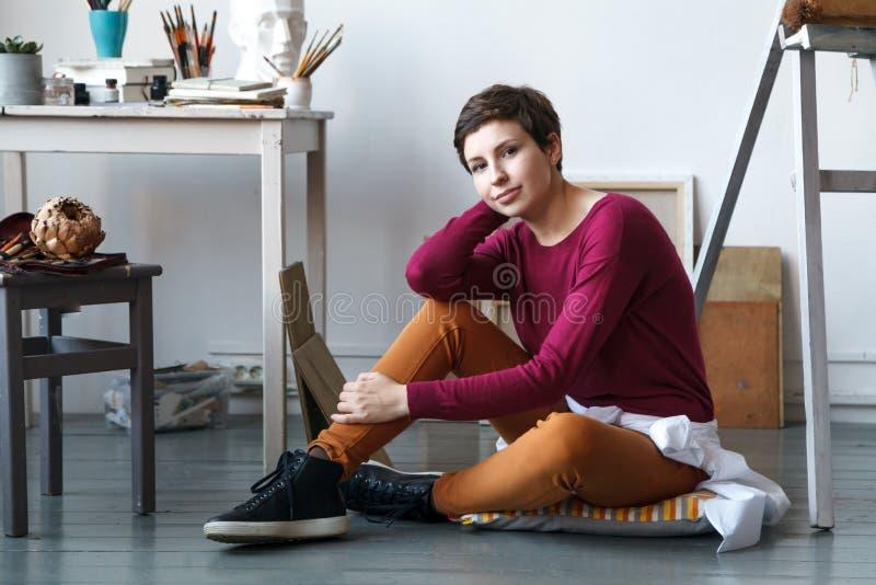 Vrouwelijke kunstenaar in haar ruime witte studio stock afbeelding