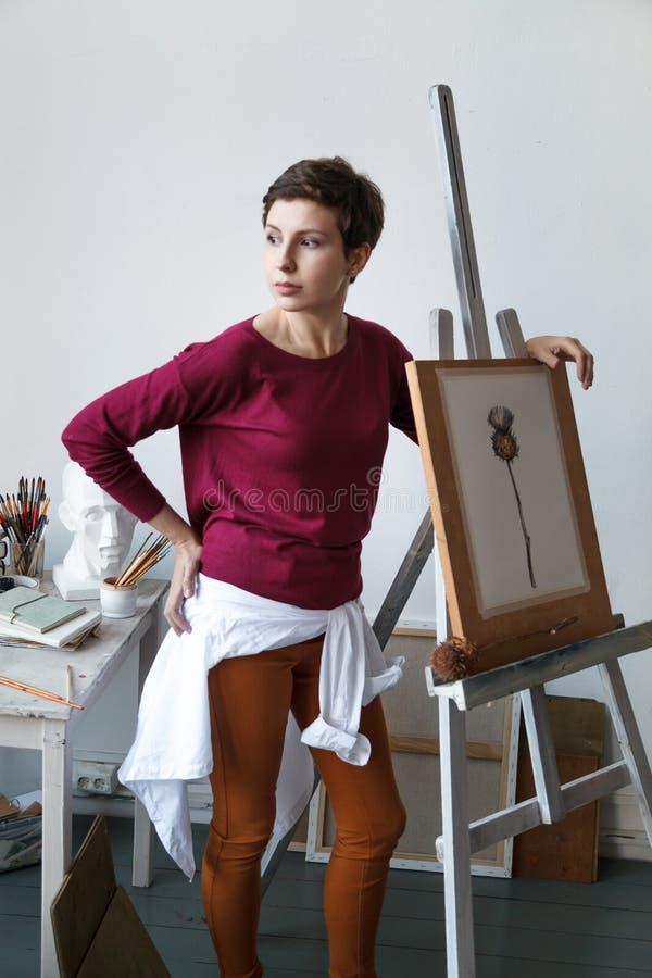 Vrouwelijke kunstenaar in haar ruime witte studio royalty-vrije stock afbeeldingen