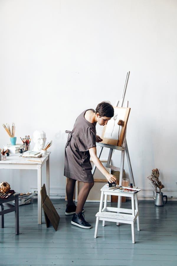 Vrouwelijke kunstenaar in haar ruime witte studio die met waterverf het schilderen werken royalty-vrije stock afbeelding