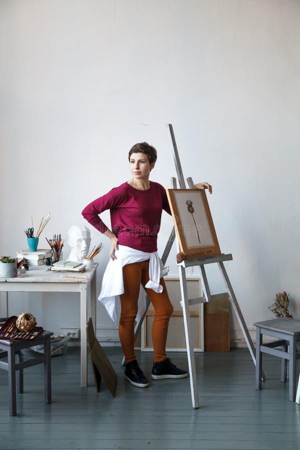Vrouwelijke kunstenaar in haar ruime witte studio die met waterverf het schilderen werken stock afbeeldingen