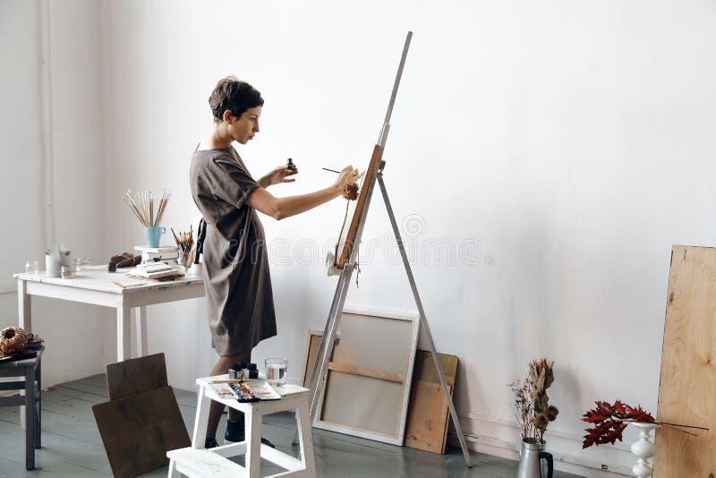 Vrouwelijke kunstenaar in haar ruime witte studio die met waterverf het schilderen werken stock foto's