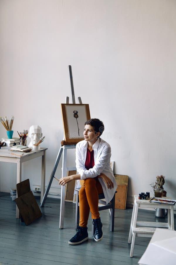 Vrouwelijke kunstenaar in haar ruime witte studio die met waterverf het schilderen werken stock fotografie