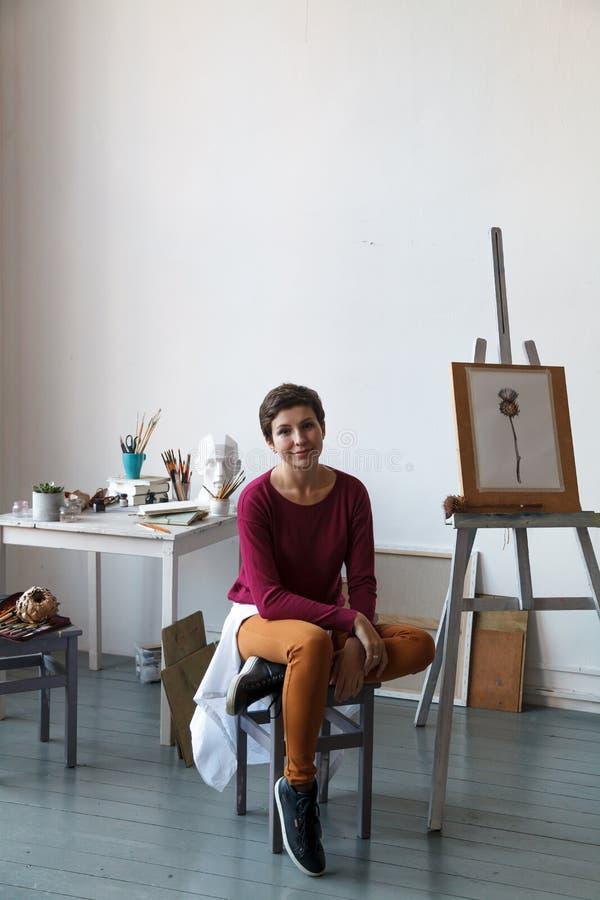 Vrouwelijke kunstenaar in haar ruime witte studio die met waterverf het schilderen werken stock foto