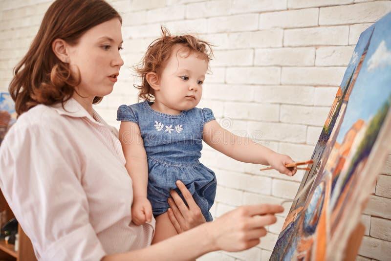 Vrouwelijke Kunstenaar Holding Little Girl in Wapens stock afbeeldingen