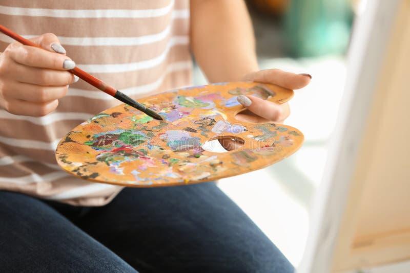Vrouwelijke kunstenaar met borstel en verfpalet in workshop stock foto's