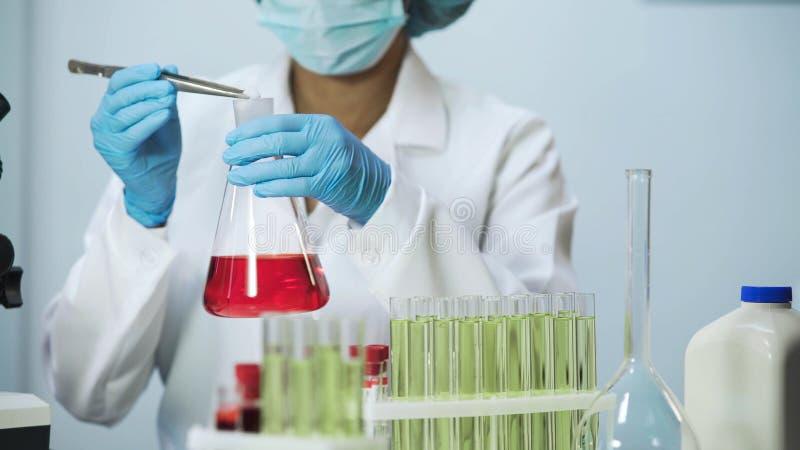 Vrouwelijke laboratorium hulp het zetten reagens in de fles, die de kosmetiekonderzoek doen royalty-vrije stock foto