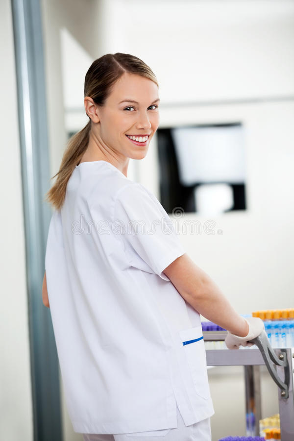 Vrouwelijke Laboratoriumtechnicus Pushing Medical Cart binnen stock fotografie
