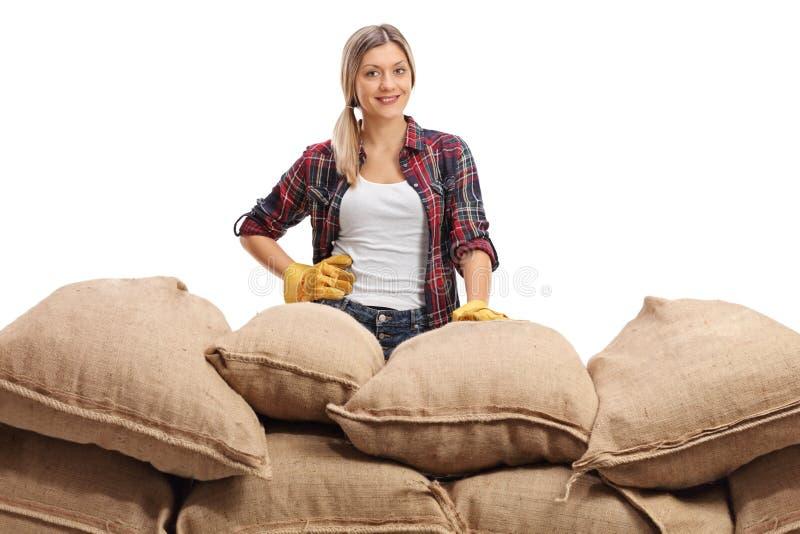 Vrouwelijke landbouwer achter een stapel van jutezakken royalty-vrije stock afbeelding