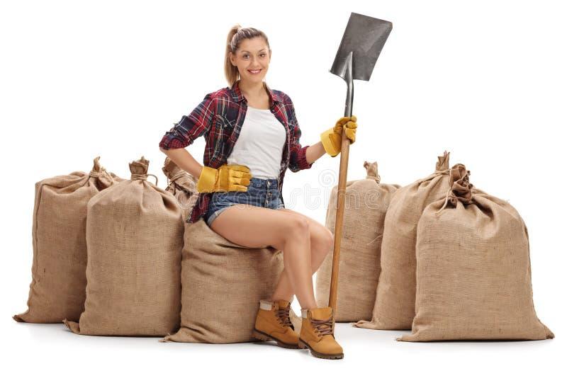 Vrouwelijke landbouwer die een schop houden en op jutezakken zitten royalty-vrije stock foto