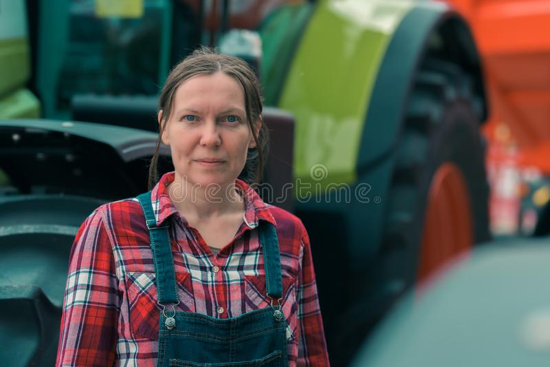 Vrouwelijke landbouwer en landbouwtrekker royalty-vrije stock fotografie