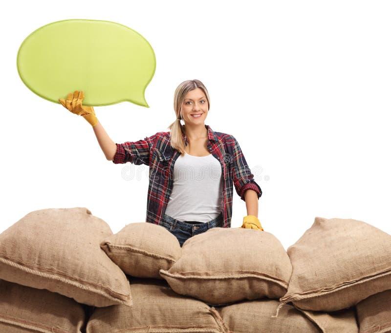 Vrouwelijke landbouwer met toespraakbel achter jutezakken stock afbeelding