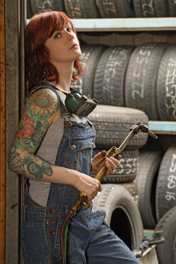 Vrouwelijke lasser met tatoegeringen stock fotografie