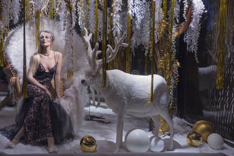 Vrouwelijke ledenpop in peignoir en een wit hert op het venster van de Kerstmiswinkel royalty-vrije stock afbeelding