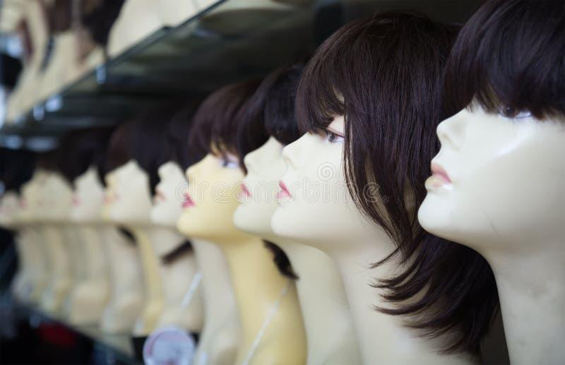 Vrouwelijke ledenpoppen met pruiken op planken van haarsalon stock foto