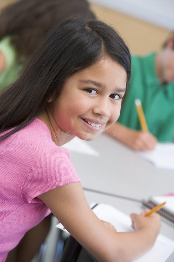 Vrouwelijke leerling in basisschoolklaslokaal stock foto's