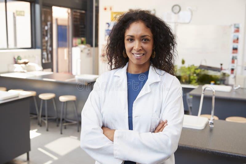 Vrouwelijke leraar die in laboratoriumlaag in de ruimte van de schoolwetenschap glimlachen stock foto's