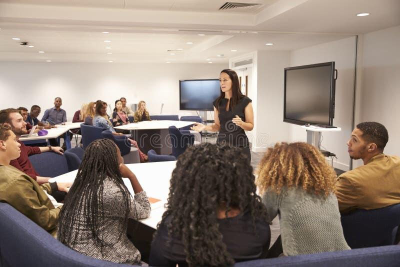 Vrouwelijke leraar die universitaire studenten in een klaslokaal richten stock afbeeldingen