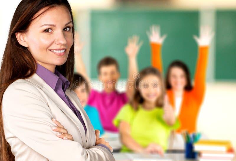Vrouwelijke leraar met kinderen bij klasse  royalty-vrije stock afbeeldingen