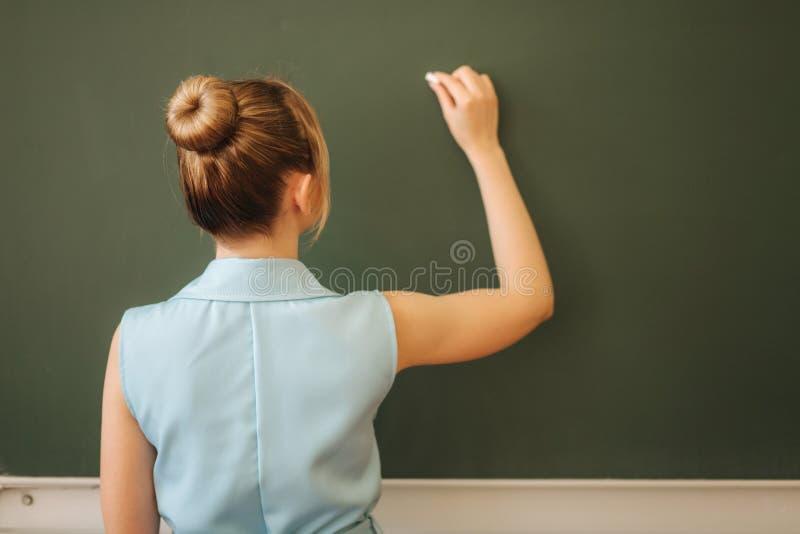 Vrouwelijke leraarswijtingen die op schoolbank thomething Jonge leraar stock foto's