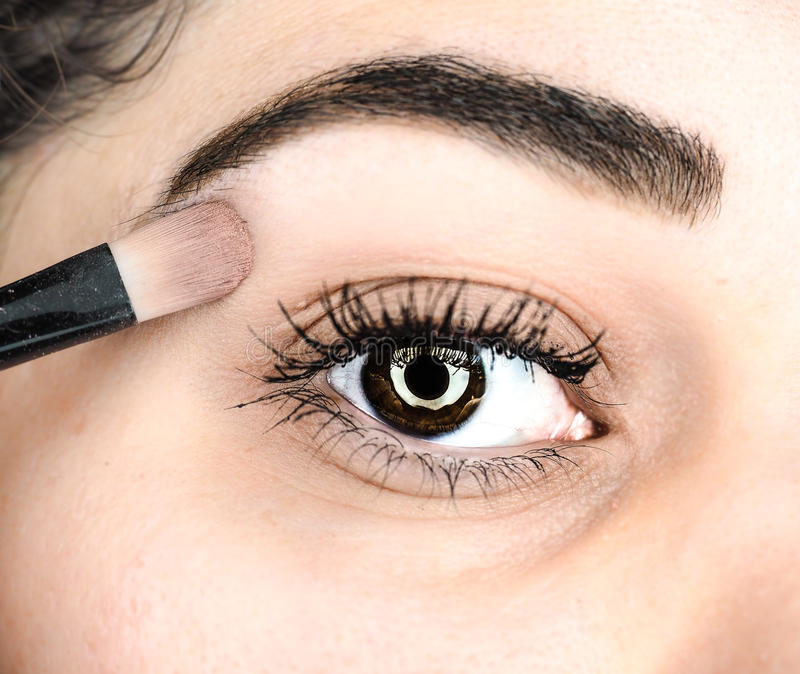 Vrouwelijke liggende definitieve aanraking van make-up bij extreme close-up royalty-vrije stock foto's