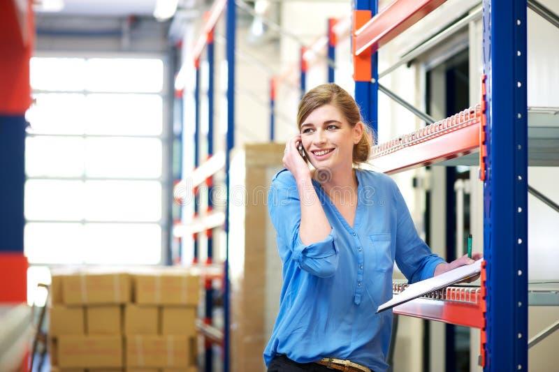 Vrouwelijke logistiekarbeider het controleren voorraad en het spreken op cellphone in pakhuis royalty-vrije stock afbeelding