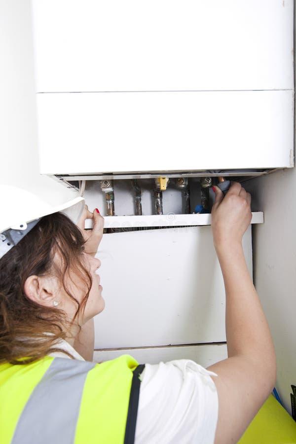 Vrouwelijke loodgieter die centrale verwarmingboiler onderhouden stock afbeelding