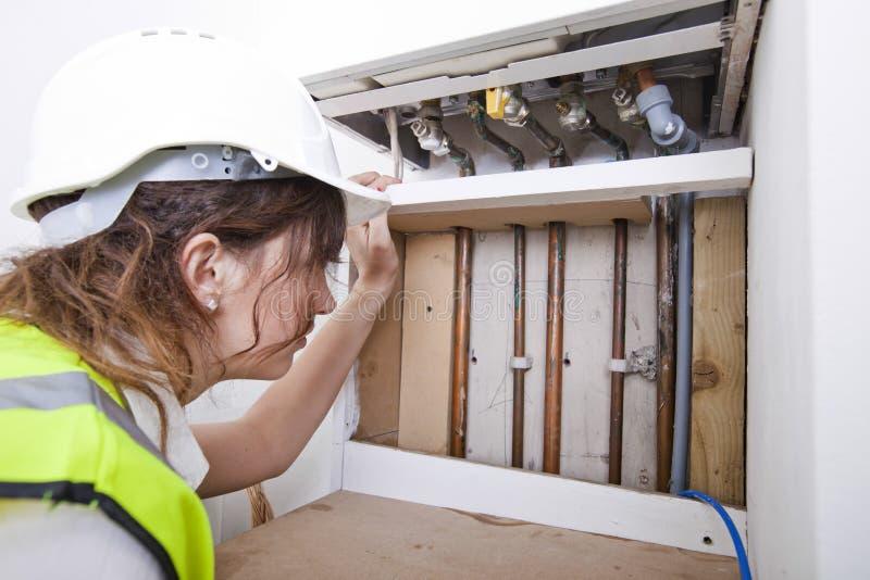 Vrouwelijke loodgieter die pijpen van centrale verwarmingboiler onderzoeken royalty-vrije stock afbeeldingen