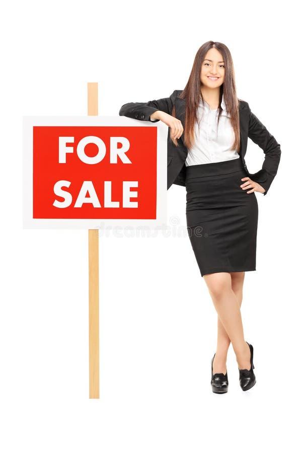 Vrouwelijke makelaar in onroerend goed die op a voor verkoopteken leunen stock foto's