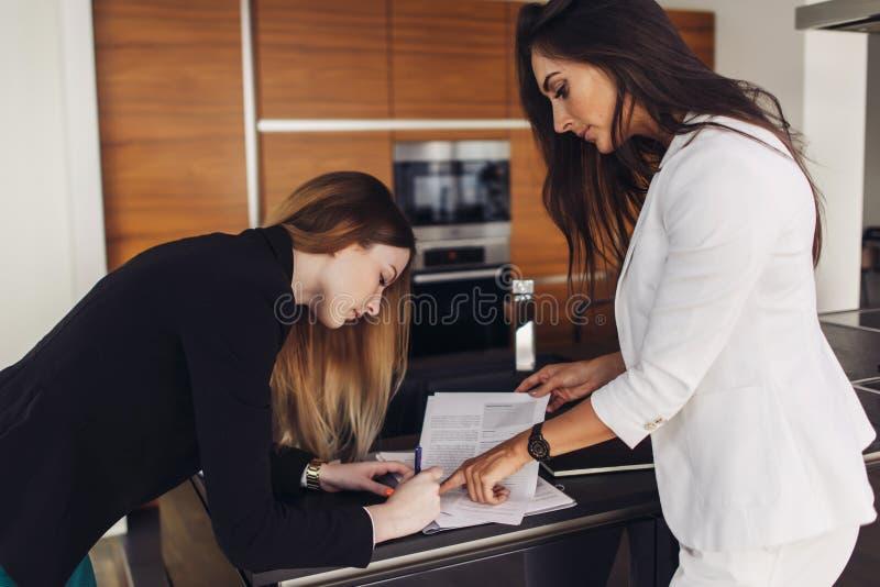 Vrouwelijke makelaar in onroerend goed en klant die wooncontract voor verkoop en aankoop ondertekenen die zich in keuken van nieu stock afbeelding