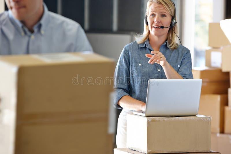 Vrouwelijke Manager die Hoofdtelefoon in het Pakhuis van de Distributie met behulp van stock foto's