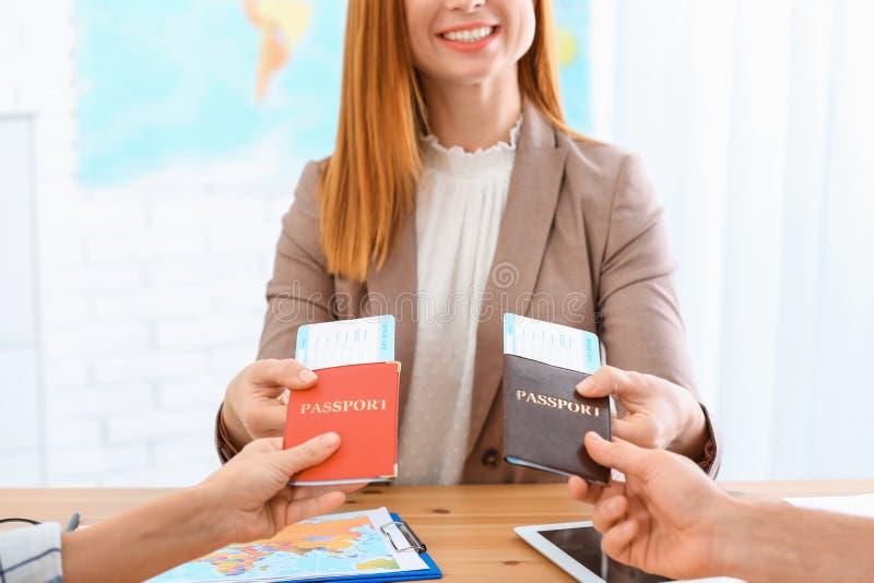 Vrouwelijke manager die paspoorten met kaartjes geven aan cliënten in reisbureau stock afbeelding
