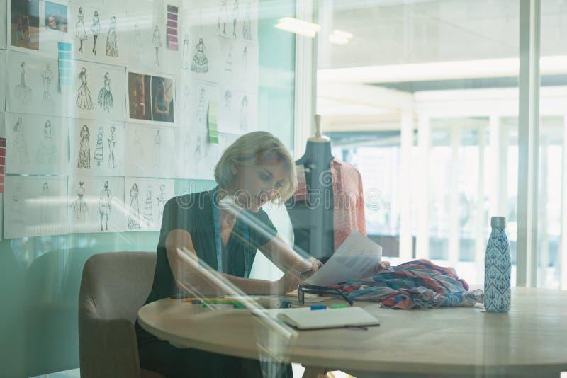 Vrouwelijke manierontwerper die bij bureau in ontwerpstudio werken royalty-vrije stock foto's