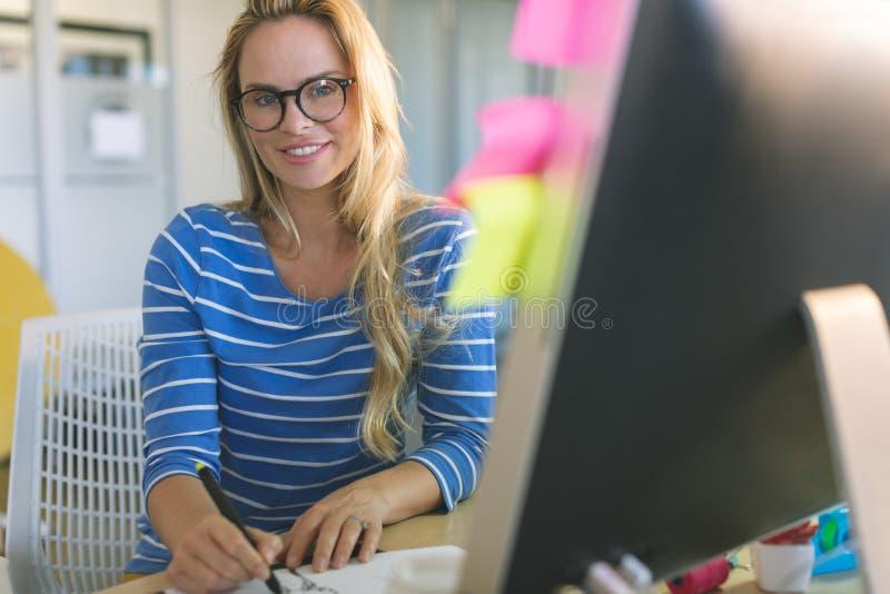 Vrouwelijke manierontwerper die camera bekijken terwijl het trekken van schetsen bij bureau royalty-vrije stock afbeeldingen