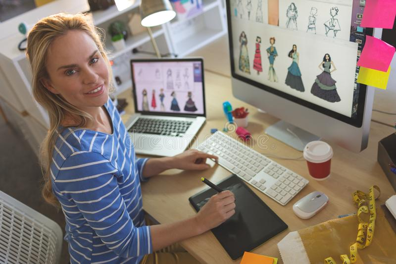 Vrouwelijke manierontwerper die camera bekijken terwijl het werken bij bureau royalty-vrije stock afbeeldingen